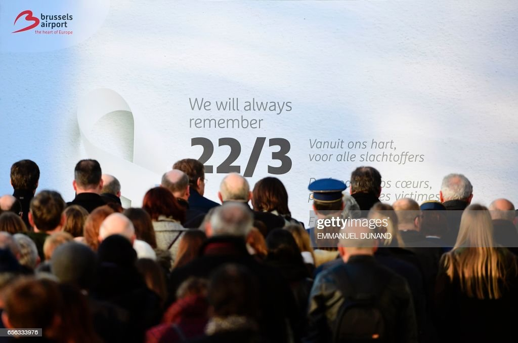 TOPSHOT - People observe a minute of silence at Brussels' international airport in Zaventem during a memorial ceremony to mark the first anniversary of the twin Brussels attacks by Islamic extremists on March 22, 2017. Belgium marks the first anniversary of the Islamic State bombings in Brussels, one at the airport and the other in the metro, in which 32 people were killed and more than 320 wounded with ceremonies showing that the heart of Europe stands defiant. / AFP PHOTO / Emmanuel DUNAND