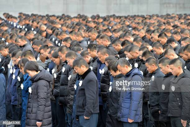 People observe a minute of silence during the state ceremony for the Nanjing Massacre at the Nanjing Massacre Museum on December 13 2017 in Nanjing...