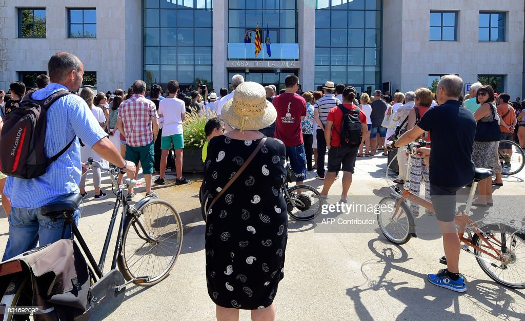 People observe a minute of silence for the victims of the Barcelona attack in front of Cambrils City Hall on August 18, 2017, a day after a van ploughed into the crowd, killing 13 persons and injuring over 100 on the Rambla in Barcelona. Drivers have ploughed on August 17, 2017 into pedestrians in two quick-succession, separate attacks in Barcelona and another popular Spanish seaside city, leaving 13 people dead and injuring more than 100 others. In the first incident, which was claimed by the Islamic State group, a white van sped into a street packed full of tourists in central Barcelona on Thursday afternoon, knocking people out of the way and killing 13 in a scene of chaos and horror. Some eight hours later in Cambrils, a city 120 kilometres south of Barcelona, an Audi A3 car rammed into pedestrians, injuring six civilians -- one of them critical -- and a police officer, authorities said. /