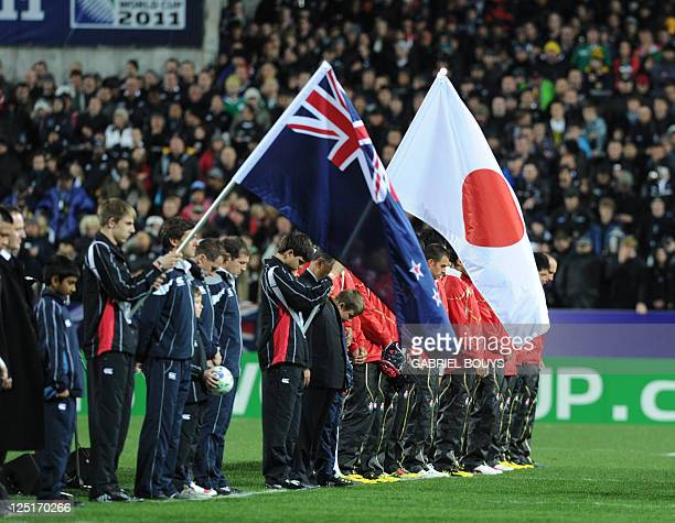 People observe a minute of silence for the victims of the earthquake and tsunami in Japan before the 2011 Rugby World Cup pool A match New Zealand vs...