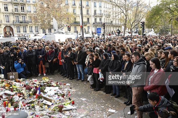 People observe a minute of silence on November 16 2015 at the Bataclan concert hall in Paris to pay tribute to victims of the attacks claimed by...