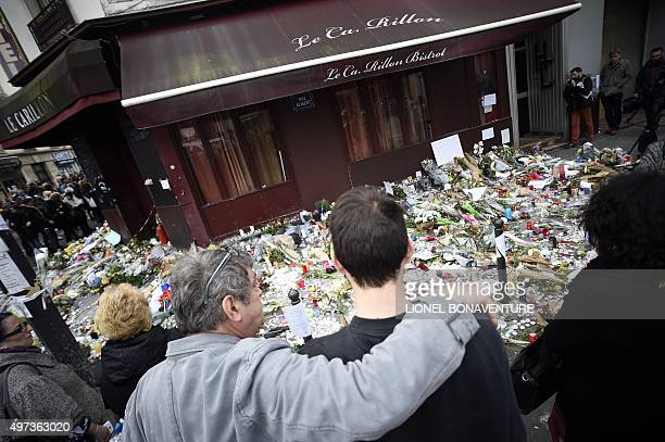 People observe a minute of silence on November 16 2015 in front of the Le Carillon cafe in Paris to pay tribute to victims of the attacks claimed by...