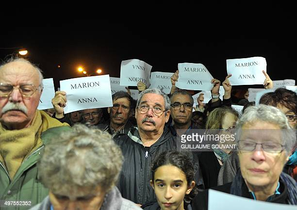 People observe a minute of silence outside the city hall in Chailles near Blois central France on November 17 to pay tribute to Anna and Marion...