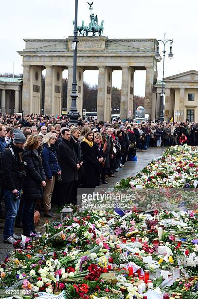 People observe a minutes silence outside the French embassy with the Brandenburg Gate in background in Berlin on November 16 2015 three days after...
