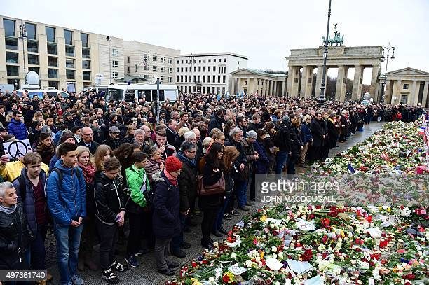 People observe a minutes silence outside the French embassy with the Brandenburg Gate in background in Berlin, on November 16, 2015 three days after...