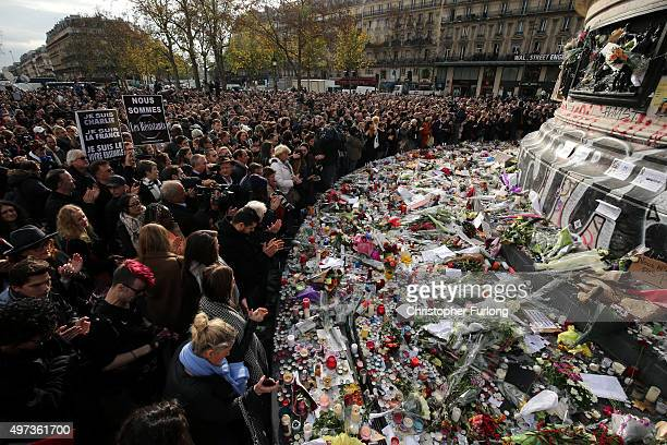 People observe a minutesilence at the Place de la Republique in memory of the victims of the Paris terror attacks last Friday on November 16 2015 in...