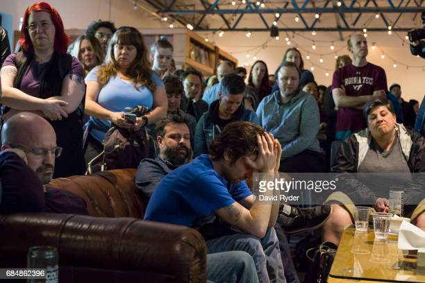 People observe a moment of silence during a memorial for musician Chris Cornell at the KEXP radio studio on May 18 2017 in Seattle Washington...
