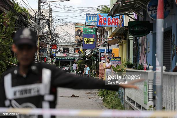 People observe as a Thai police officer stands at the site of an explosion on Friday August 12 2016 in Hua Hin Thailand A series of coordinated...