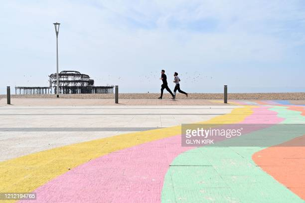 People observe social distancing as they excercise along the beachfront in Brighton on May 8 as the nation celebrates the 75th anniversary of VE Day...