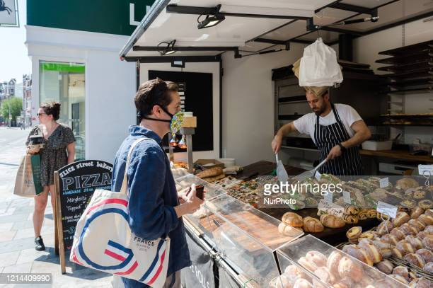 People observe social distancing as they pick up their take away orders from 'SLICE' street bakery stall in Battersea southwest London on 21 May 2020...