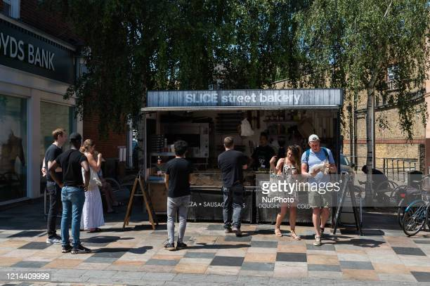 People observe social distancing as they queue in front of 'SLICE' street bakery stall in Battersea southwest London on 21 May 2020 in London England...
