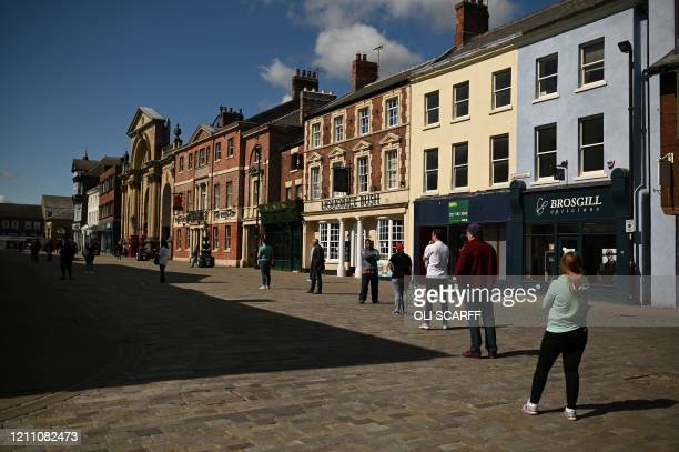 People observe social distancing guidelines standing two meters apart as they queue to enter shops and banks in Pontefract northern England on April...