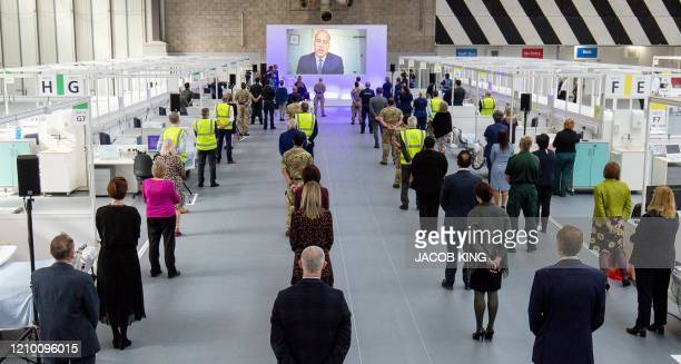 People observe social distancing measures as they stand amongst Hospital cubicles as a giant screen displays an image of Britain's Prince William...