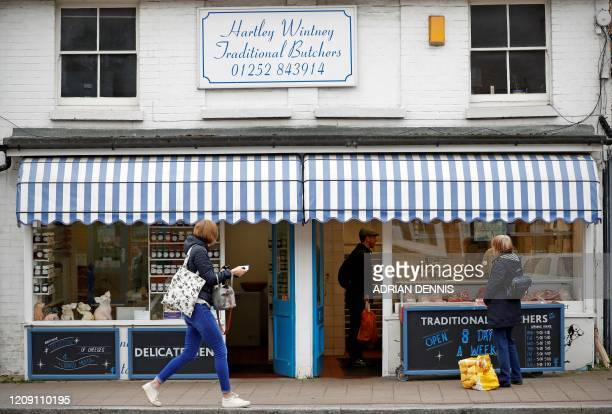 People observe social distancing while shopping for meat at the butchers shop in Hartley Wintney village in Hampshire on April 04, 2020. As life...