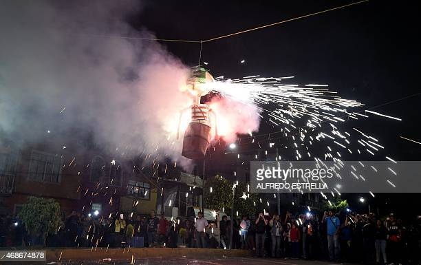 People observe the Burning of Judas a celebration held on Holy Week at the La Merced neighbourhood in Mexico City on April 4 2015 For many years...