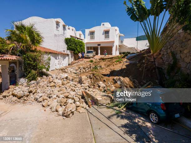 People observe the damages caused on the street and a car after a wall was knocked down after a magnitude 7.1 earthquake hit yesterday close to 9:00...