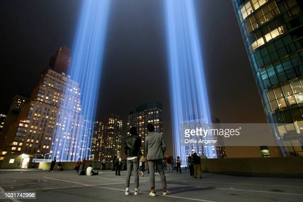People observe the 'Tribute in Light' atop the Battery Parking Garage as it rises skyward in Lower Manhattan September 11 2018 in New York City In...