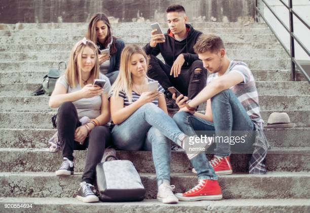 people obsessed with their smartphones - adolescente imagens e fotografias de stock