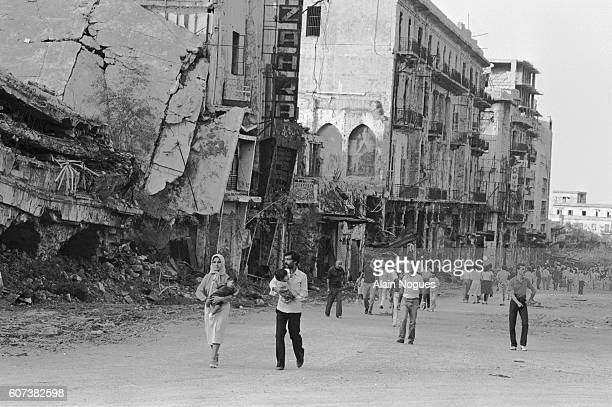 People of Beirut stroll along destroyed and damaged buildings. The ruins testify to the intense fighting going on in the city since June 1982 as a...