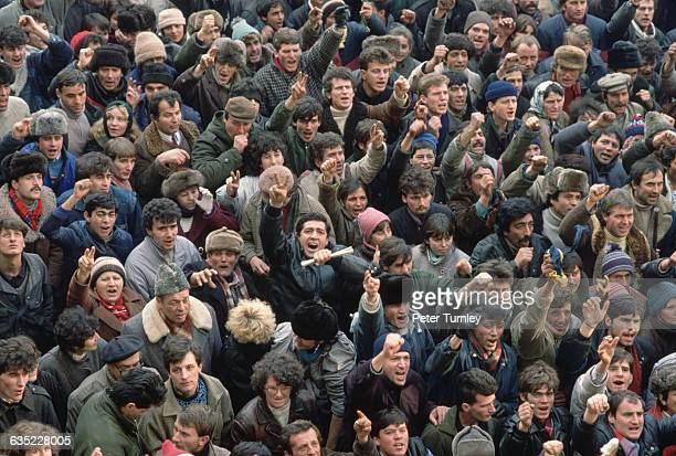 People of Bucharest shouting and flashing victory signs gather at a a prorevolutionary demonstration during the revolution of December 1989