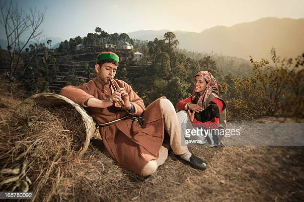 people of himachal pradesh: man playing flute and woman listening - bamboo instrument stock photos and pictures