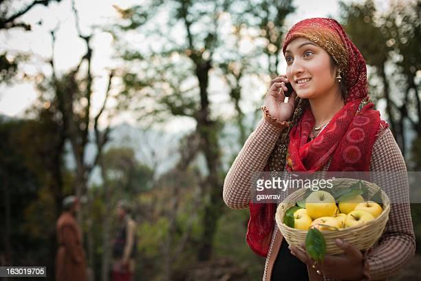 People of Himachal Pradesh: Woman on phone holding apple basket