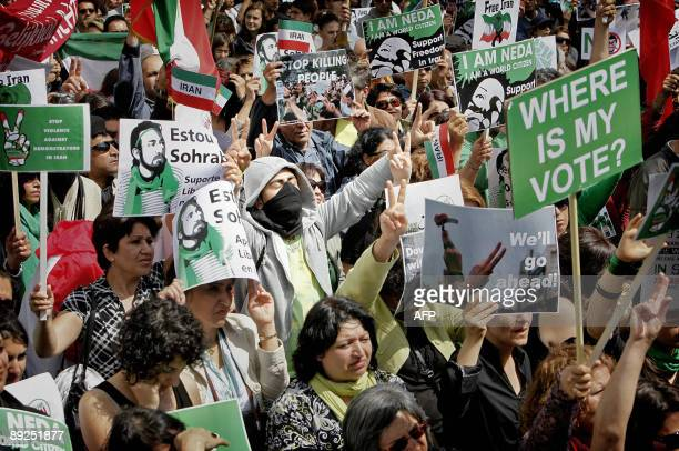 People of Iranian origin hold signs and flags during a demonstration against the Iranian regime and the recent disputed presidential elections at...