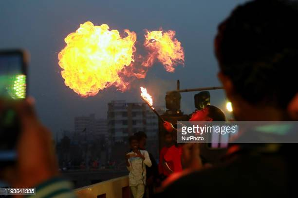 People of Old Dhaka are playing fire splitting using kerosene oil on the rooftop of their building on the occasion of Shakrain festival in Dhaka...