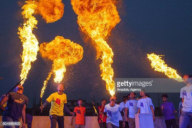 People of Old Dhaka play fire spitting using kerosene oil on the rooftop of their building on the occasion of Shakrain festival in Dhaka on January...
