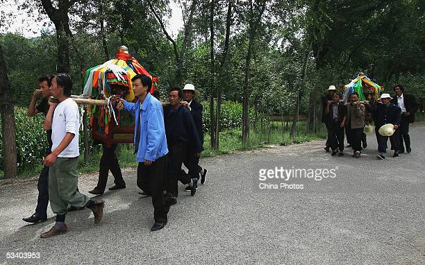 People of Tu ethnic minority group carry models of sedan chairs consecrated to gods during a worship ceremony of the Nadun Festival at Xiakou Village...