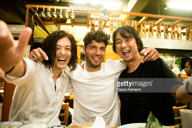 people of various ethnicities interacting at a japanese izakaya - asia pac stock pictures, royalty-free photos & images
