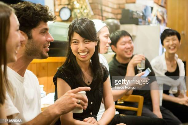 people of various ethnicities interacting at a japanese pub - asia pac stock pictures, royalty-free photos & images