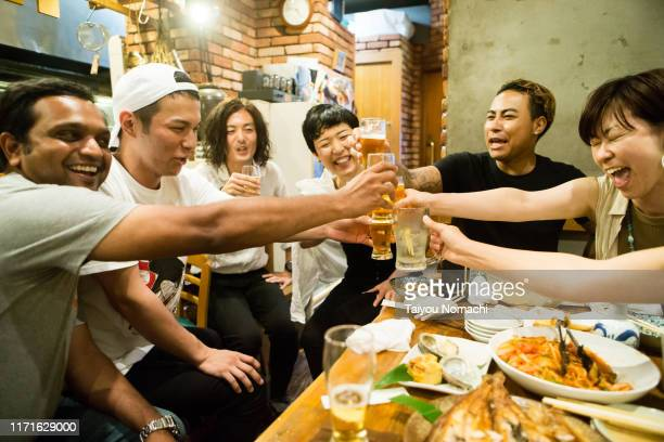people of various ethnicities interacting at a japanese pub - 乾杯 ストックフォトと画像