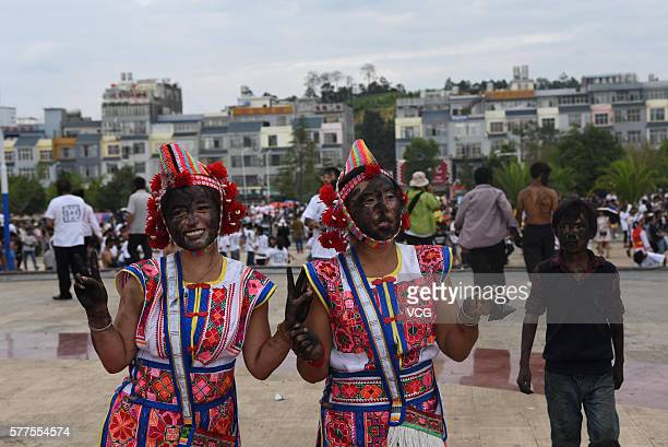 People of Yi ethnic group who are daubed rice ash pose during the Face Painting Festival in Puzhehei Resort of Qiubei County on July 18, 2016 in...