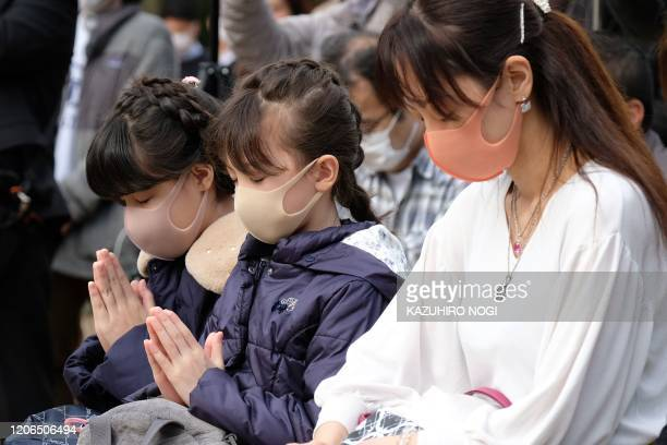 People offer a silence of moment for the victims of the 2011 earthquake and tsunami disaster at a park in Tokyo on March 11 2020 on the ninth...