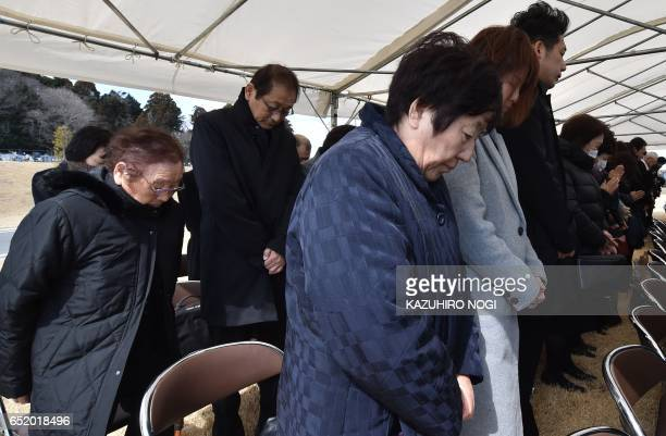 People offer a silent prayer for victims of the 2011 quaketsunami disaster during a memorial service in Namie no entry zone in Fukushima prefecture...