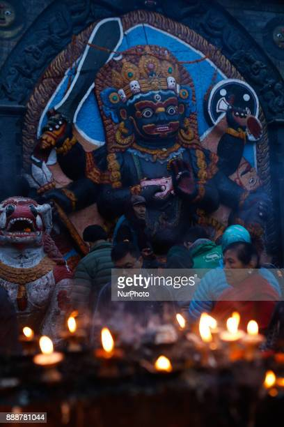 People offer butter light as they pray to the idol of god Kaal Bhairav at Kathmandu Darbar Square a UNISCO World Heritage site in Kathmandu Nepal...
