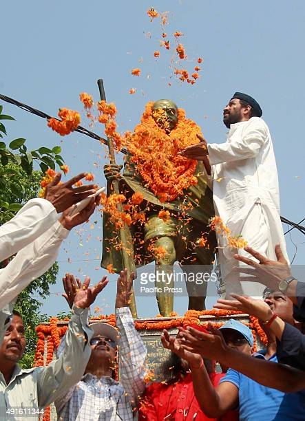 People offer floral prayers on the statue Mahatma Gandhi during his birth anniversary in Allahabad