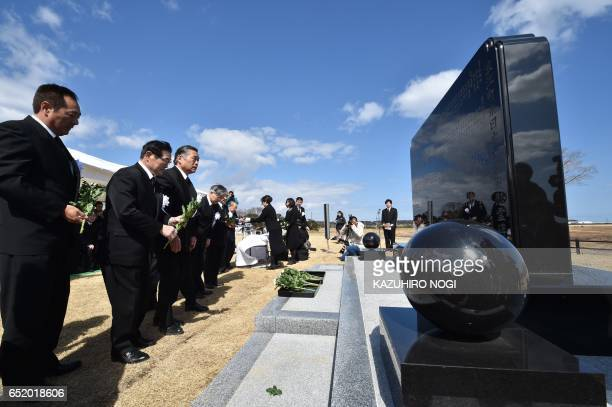 TOPSHOT People offer flowers at the monument of the victim of the 2011 quaketsunami disaster during a memorial service in Namie a no entry zone in...