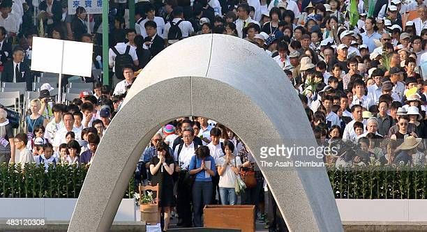 People offer prayer in front of the cenotaph during the memorial ceremony on the 70th anniversary of the Hiroshima Atomic Bomb at Hiroshima Peace...