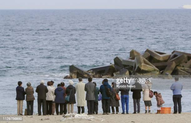 People offer prayers at a beach in Sendai Miyagi Prefecture on March 10 a day before the eighth anniversary of the 2011 earthquaketsunami disaster in...