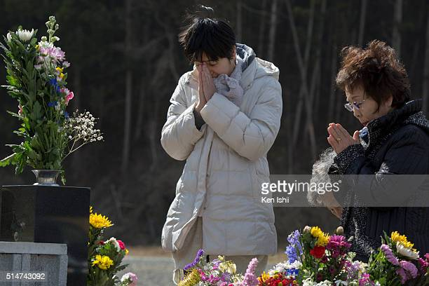 People offer prayers at Okawa Elementary School on March 11 2016 in Ishinomaki Japan Today marks the fifth anniversary of the magnitude 90 earthquake...