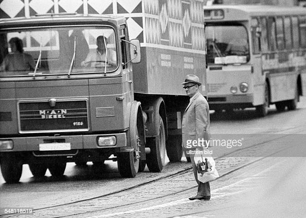 People, older man with shopping bag stands in the middle of a traffic road and tries to cross the road, heavy traffic, aged 65 to 75 years -