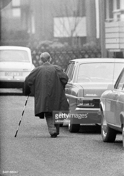 People, older people, older man with a blindmans stick walks on the street and passes some cars, aged 60 to 70 years -