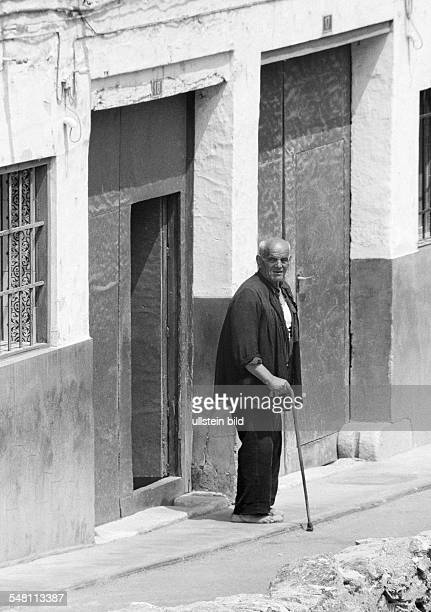 people older people older man with a walking stick stands in front of a house door barefooted aged 70 to 80 years Spain Valencia