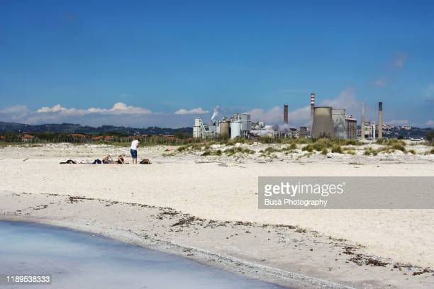 people on a beach near a factory plant in tuscany, italy, as seen from the coastline - as stock pictures, royalty-free photos & images
