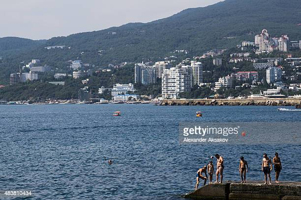 People on a beach on August 11 2015 in Yalta Crimea Russian President Vladimir Putin signed a bill in March 2014 to annexe the Crimean peninsula but...