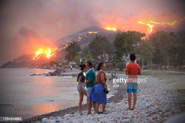 People on a beach watch the blazes spreading up a hill in the Aegean coast city of Oren, near Milas, in the holiday region of Mugla on August 3, 2021...