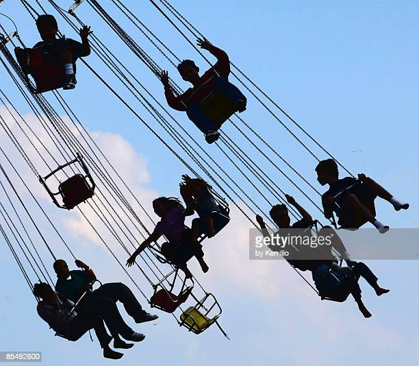 people on a carnival ride in silhouette - ken ilio stock photos and pictures