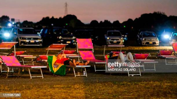 """People on a deckchair and in their car watch Italian comedy """"Tolo Tolo"""" directed by Checco Zalone on July 9, 2020 on the opening night of Europe's..."""